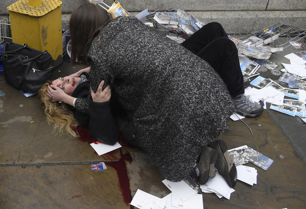 Witnessing the Immediate Aftermath of an Attack in the Heart of London © Toby Melville, Reuters // A passerby comforts an injured woman lying on the pavement after Khalid Masood drove his car into pedestrians killing four in addition to a police officer at Westminster Bridge in London, Britain, March 22, 2017.